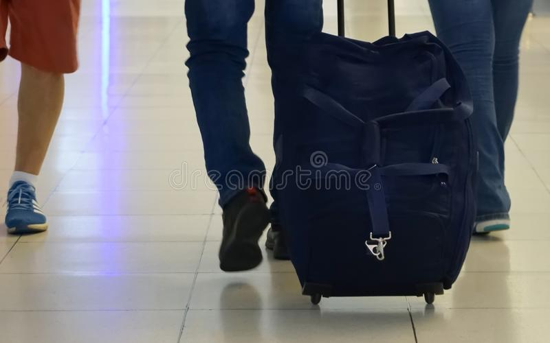 Back view of travel luggage hold on passenger hand at airport royalty free stock photos