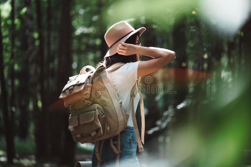 Back view on traveler backpack and hipster girl wearing hat. Young brave woman traveling alone among trees in forest on outdoors stock image