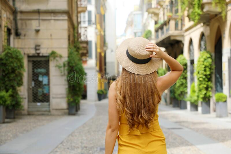 Back view of traveler fashion woman visiting Brera neighborhood in Milan, Italy stock photography