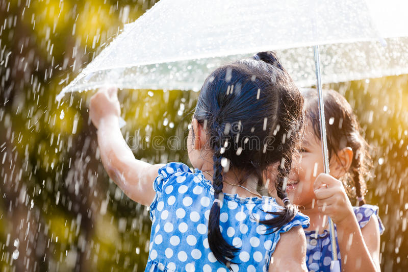 Back view of two asian little girls with umbrella. Having fun to play with the rain together in vintage color tone royalty free stock image
