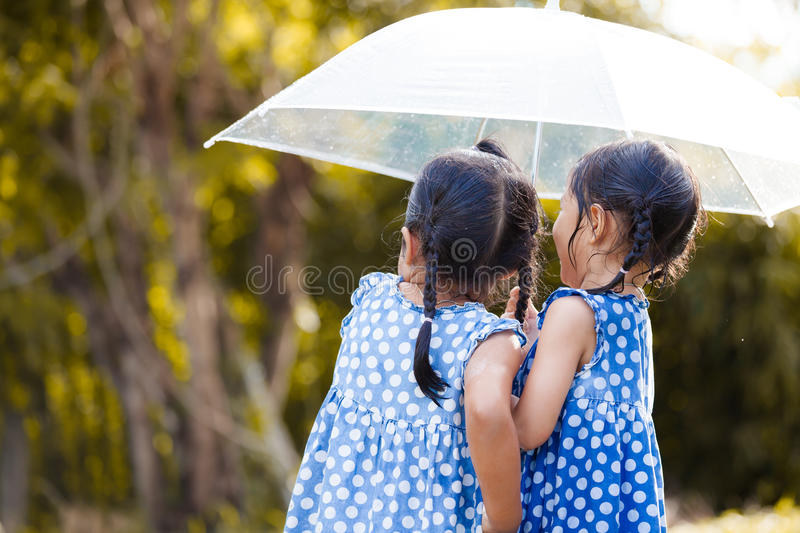Back view of two asian little girls with umbrella. Having fun to play with the rain together in vintage color tone royalty free stock photos