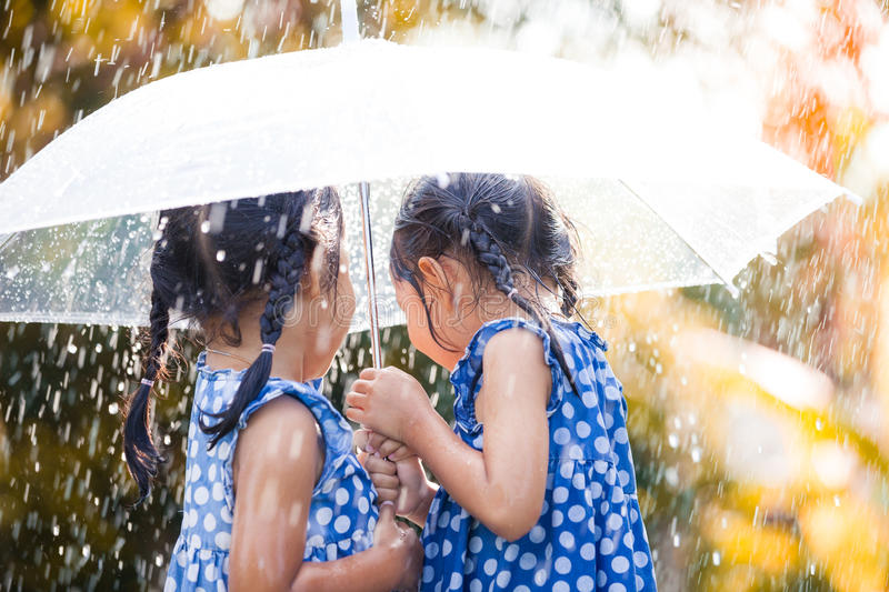 Back view of two asian little girls with umbrella. Having fun to play with the rain together in vintage color tone stock images