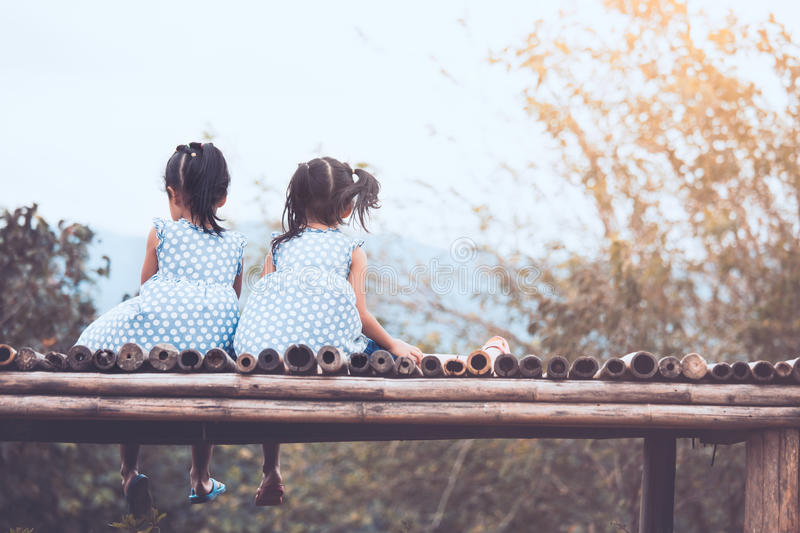 Back view of two child girls sitting and looking at nature. Together in vintage color tone stock image