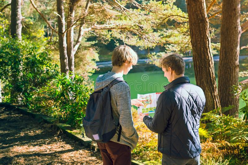 Back view two friends, brothers looking at map, navigating during camping travel hike outdoors in forest. Hiking adventure. royalty free stock photography