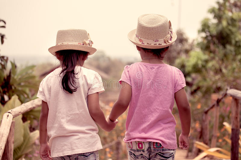 Back view of two little girls holding hand and walking together. In the garden in vintage color tone stock photo