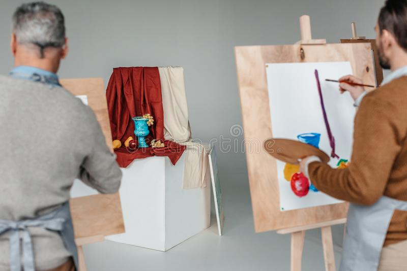 back view of two men painting still life on easels royalty free stock image