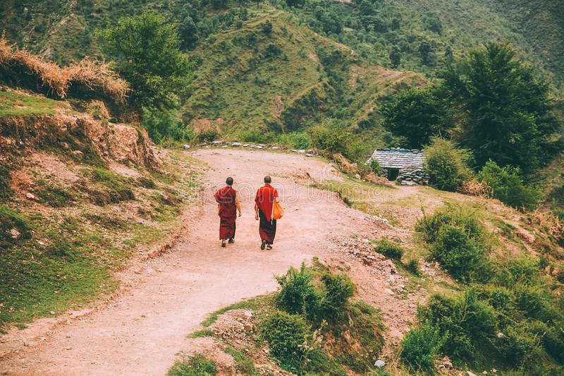 back view of two monks walking on mountain road in Indian Himalayas, stock photo