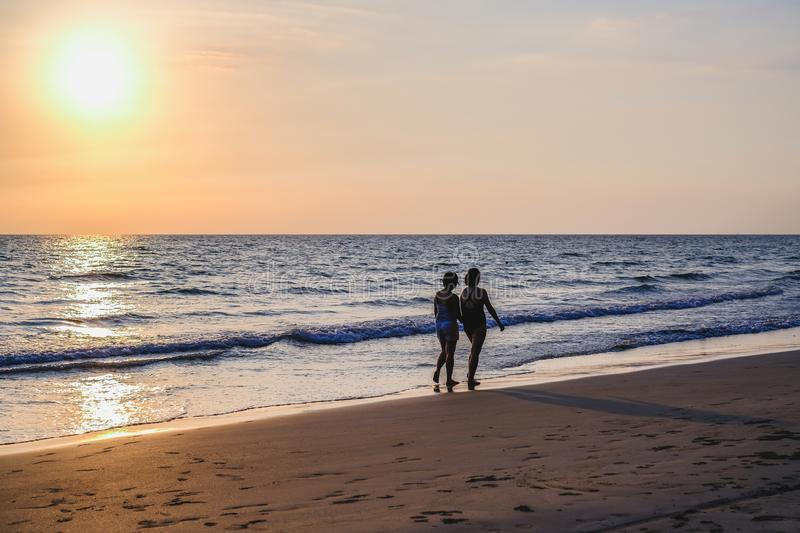 The back view of two women wearing bikinis walking on the beach vacations travel holiday. royalty free stock photo