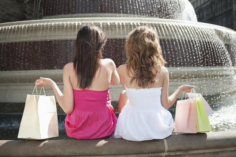 Back view of two young female friends with shopping bags sitting by water fountain royalty free stock photos