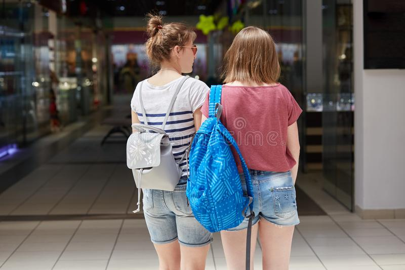 Back view of two young females with rucksack stroll in shopping mall, makes purchases, wears denim shorts and casual t shirt, try royalty free stock image