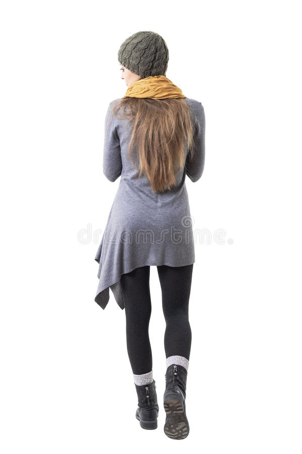 Back view of unique style hipster girl in winter clothes walking away holding scarf. Full body isolated on white background stock images