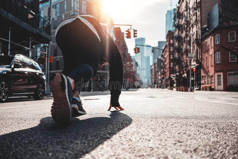 Back view on urban runner in start pose on city street. Prepearing marathon, healthy run concept royalty free stock photography