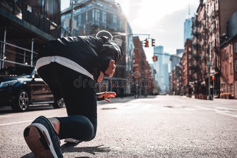 Back view on urban runner in start pose on city street stock photo