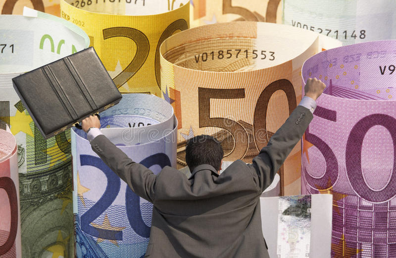 Back view of victorious businessman with briefcase against rolled up Euros royalty free stock images