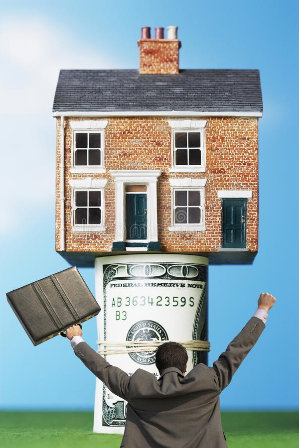 Back view of victorious businessman with briefcase in front of house on money rolls stock image
