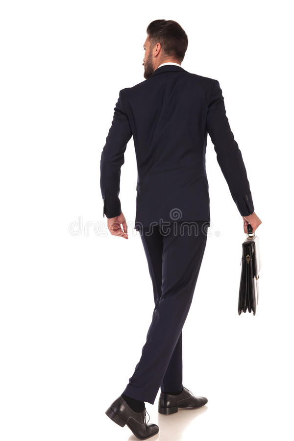 Back view of walking business man holding a briefcase. Back view of a walking business man holding a briefcase and looking to his side on white background stock photos