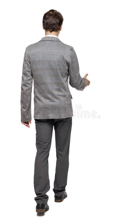 Back view of a walking businessman who stretches his hand for a handshake royalty free stock image