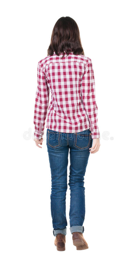 Back view of walking woman in checkered shirt. royalty free stock images