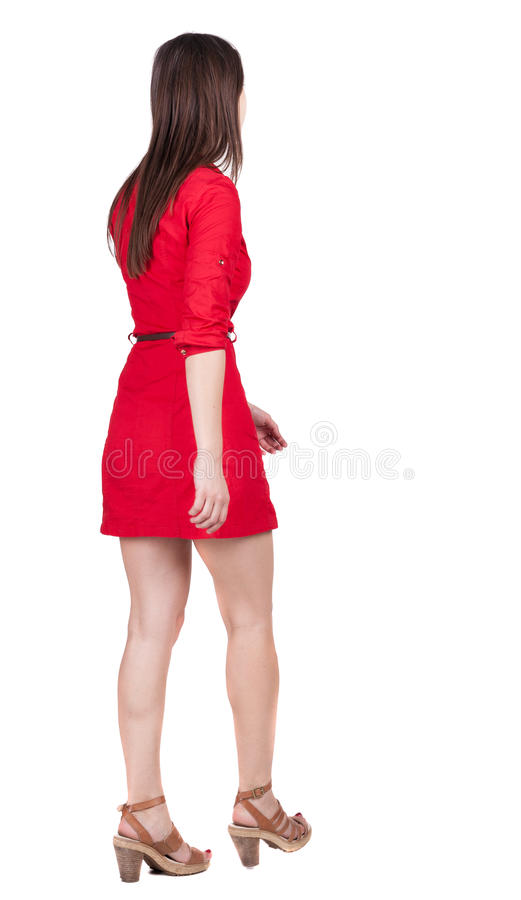 Back view of walking woman . going gir in motion. Rear view people collection. backside view of person. Isolated over white back. Ground. Girl in red short dress royalty free stock photography