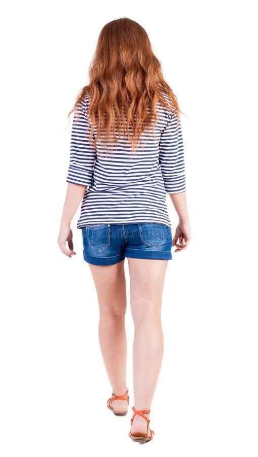Back view of walking young beautiful redhead woman stock photos