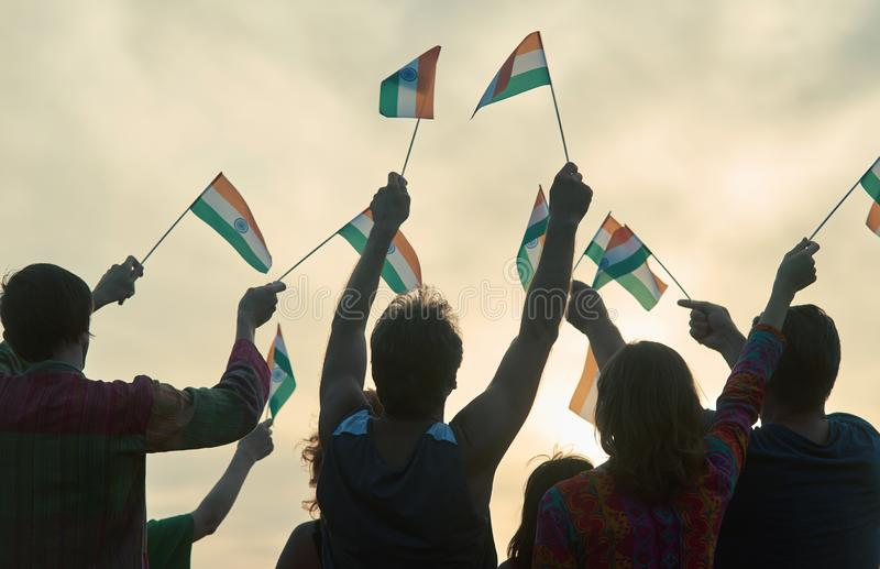 Back view waving indian flags. Patriotic family against evening sky background stock photography