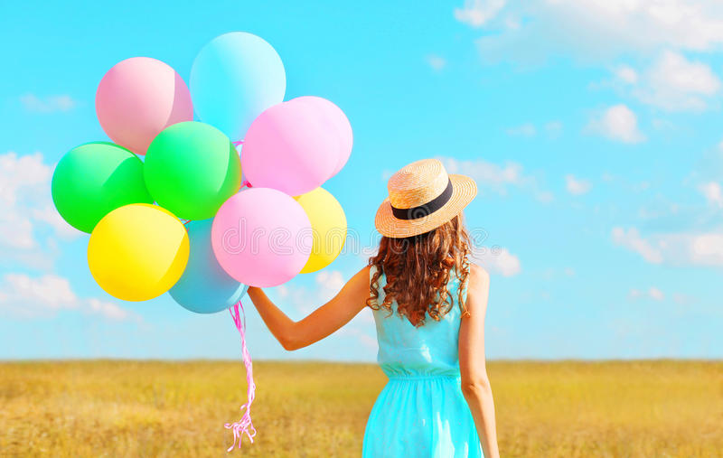 Back view woman with an air colorful balloons in a straw hat enjoying a summer day on a field and blue sky royalty free stock photos