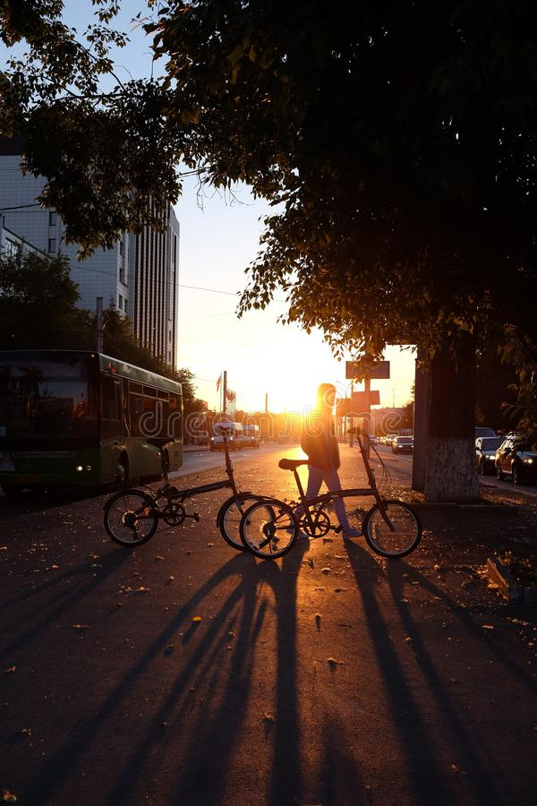 Back view of a woman with a bicycle. cyclist sits on the bike. backside view of person. sunrise sunset on road stock photo