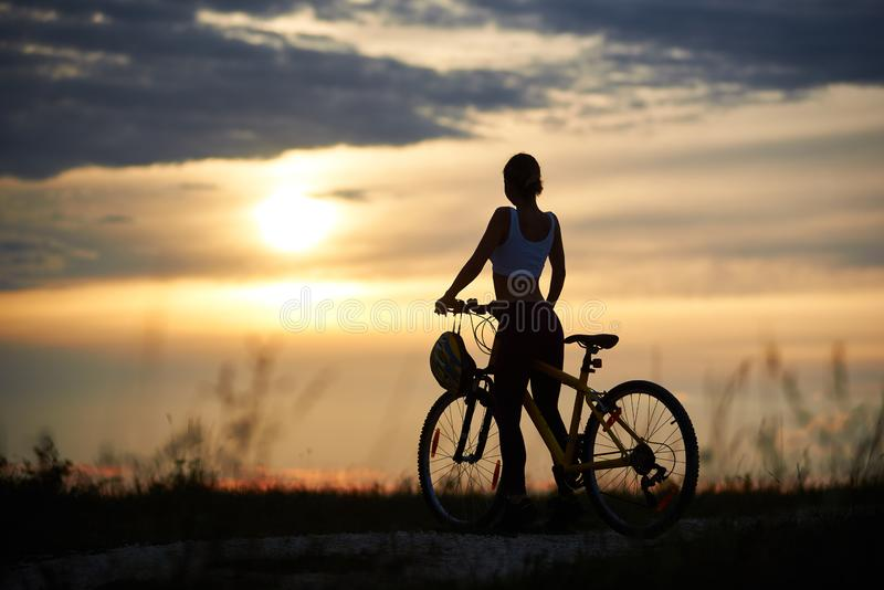 Back view of woman with bicycle standing on road among grass enjoying the sunset at evening sky. Back view of woman with bicycle standing on road among grass stock photos