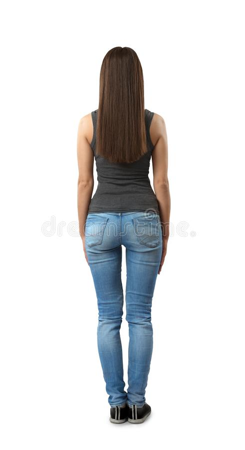 Back view of woman in gray sleeveless top and blue jeans standing with arms at sides isolated on white background. Beauty standards. Health and beauty. Dress royalty free stock photo