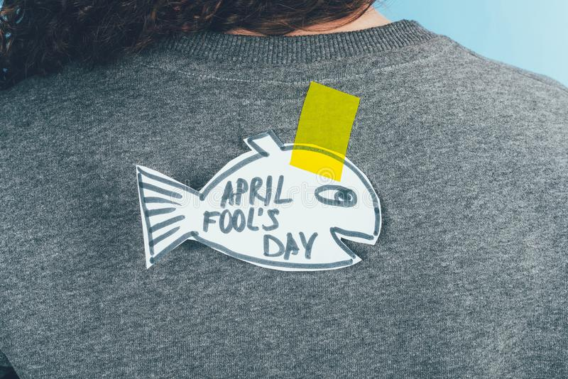Back view of woman with hand drawn fish on back, april fools day concept stock photography