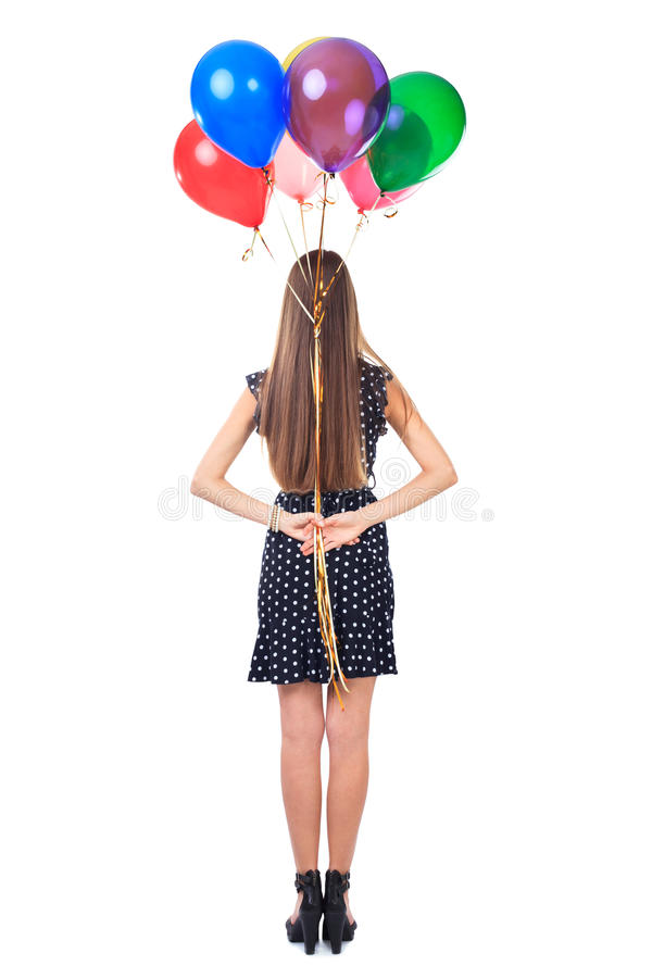 Back view of woman holding balloons behind her back. Full length back view of woman in polka dot dress holding colorful balloons behind her back isolated on stock photography
