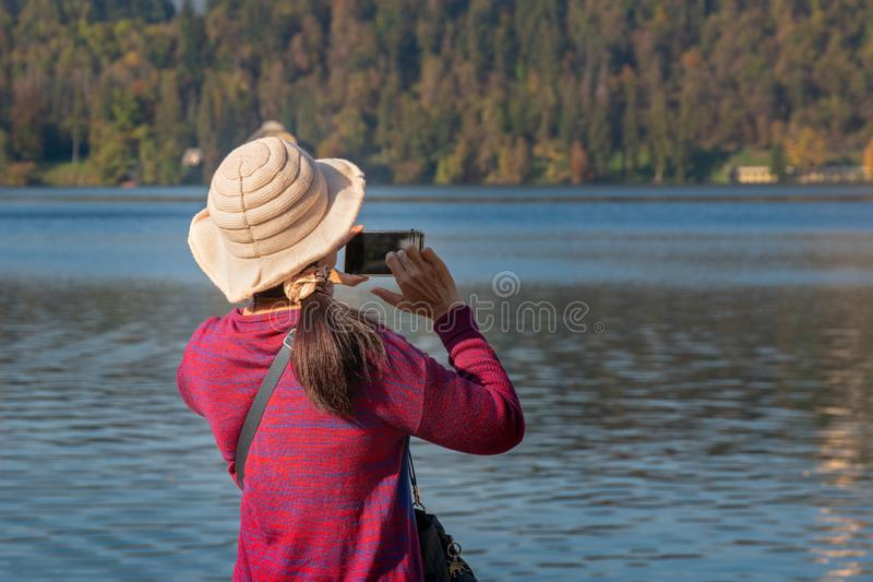 Back view of woman holding mobile phone in hands and taking photo. Of the beatifull lake Bled royalty free stock photography