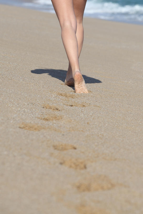 Back View Of A Woman Legs Walking On The Beach And Her Traces Royalty Free Stock Image