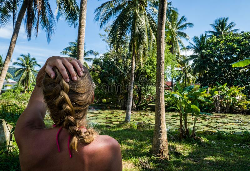 Woman looking at beautiful tropical view with palm trees and small pond. Back view of woman looking at palm trees and dense tropical vegetation growing around stock image