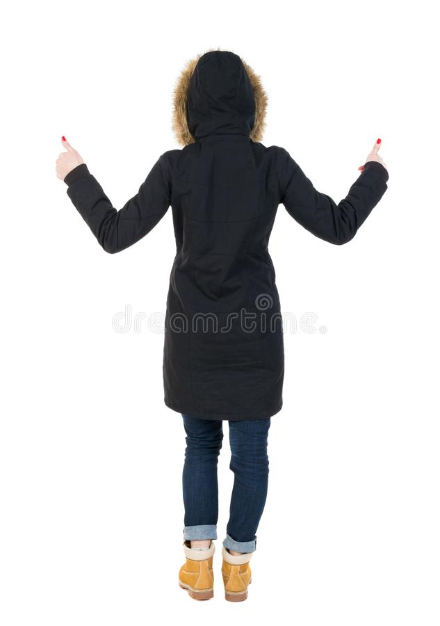 Back view of woman in parka thumbs up. Rear view people collection. backside view of person. Isolated over white background. Girl in a black winter jacket with royalty free stock images