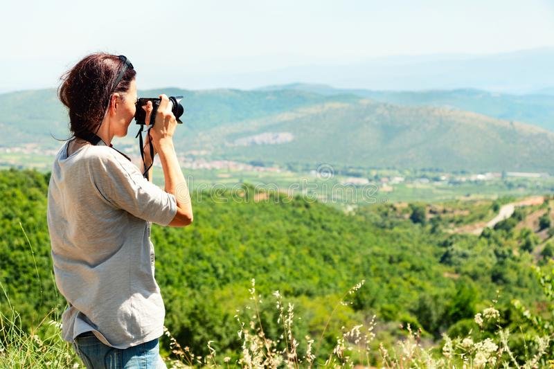 Back view of a woman photographer taking pictures of the valley with mountains from above stock images