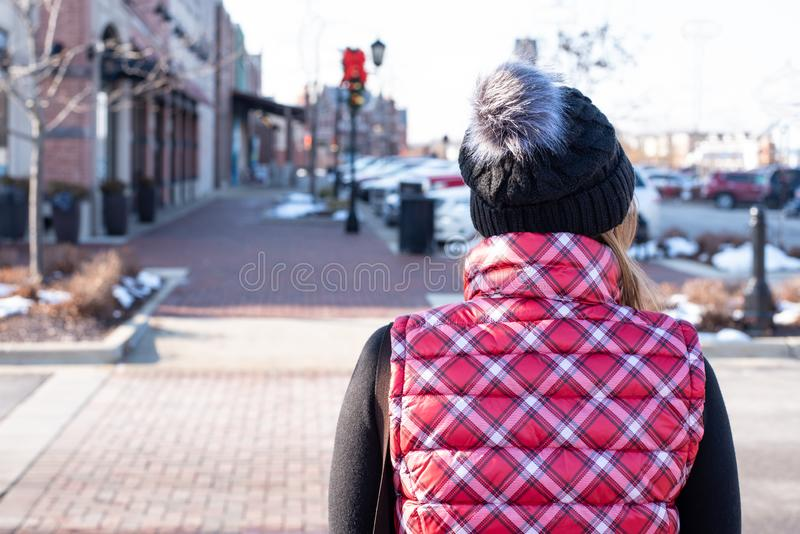 Back view of woman in plaid vest and hat walking outdoor at outlet shopping mall stock photo