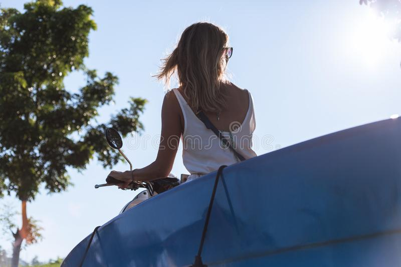 Back view of woman riding scooter with surfing board against. Blue sky stock photo