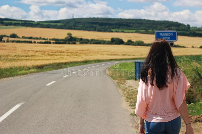 Back View of Woman on Road Against Sky stock images