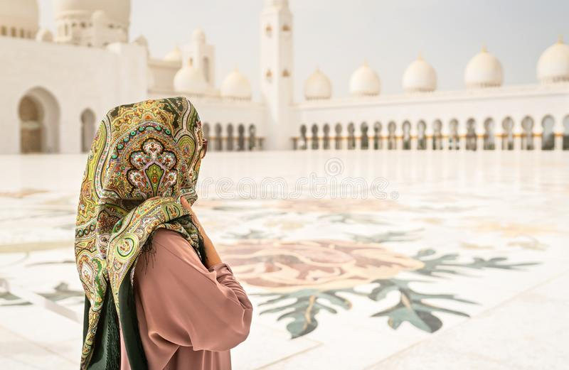 Back view of Woman in The Sheikh Zayed Grand Mosque. Traditional Muslim building in the United Arab Emirates. stock photography