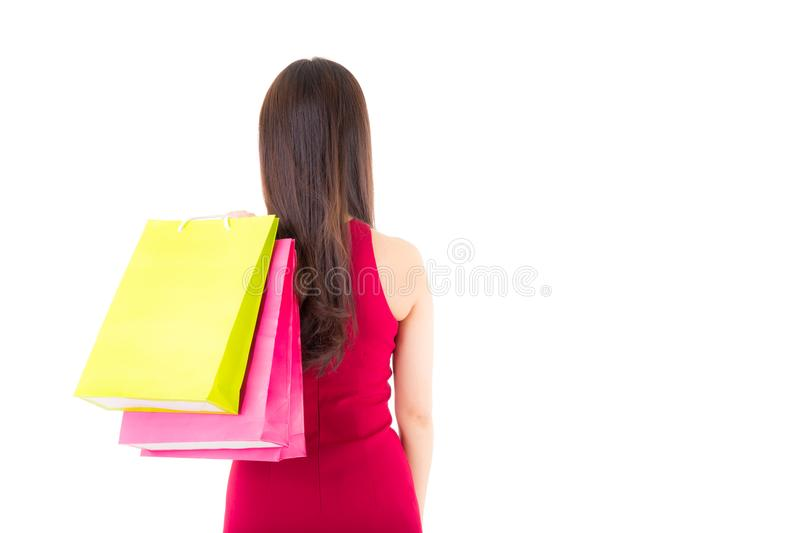 Back view of woman with shopping bags . beautiful girl in red dress standing backside view. Of person and holding paper bag Isolated on white background stock photo