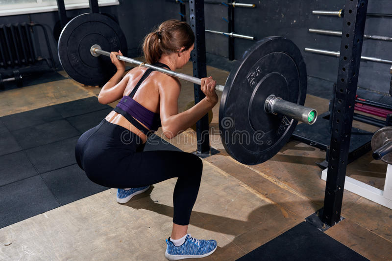 Back View of Woman in Shoulder Squat. Back view of strong young woman lifting heavy barbell performing shoulder squat during crossfit workout in modern gym royalty free stock photo