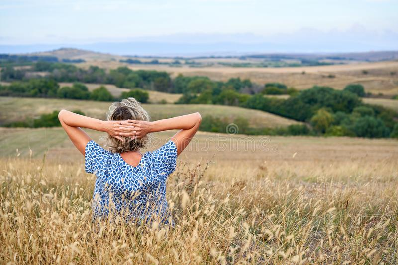 Back view of a woman sitting in dry barren grass, looking in the horizon stock images
