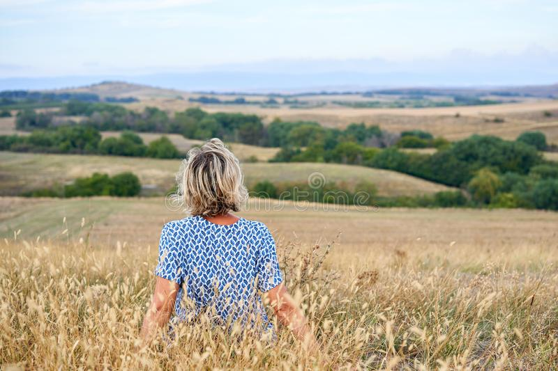 Back view of a woman sitting in dry barren grass, looking in the horizon stock image