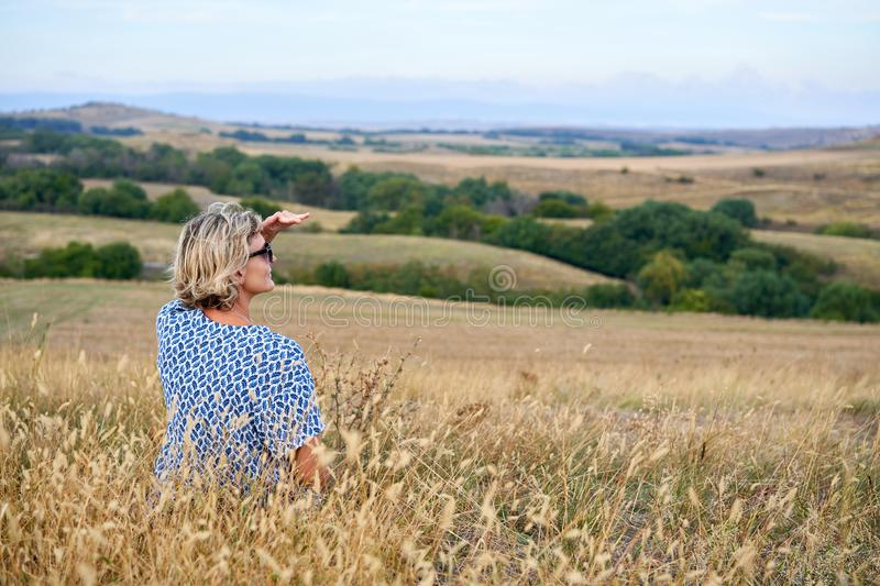 Back view of a woman sitting in dry barren grass, looking in the horizon royalty free stock image