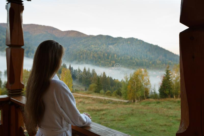 Back view of woman in spa bathrobe standing at wooden balcony of hotel resort room and enjoying beautiful morning alpain royalty free stock photos