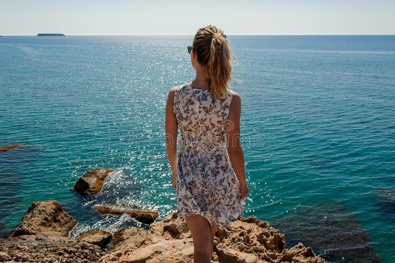 Back view woman standing on the rock in dress royalty free stock image