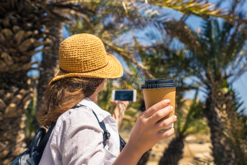 Back view on the Woman in the straw hat with paper cup of coffee taking selfie picture or video using smartphone. royalty free stock image