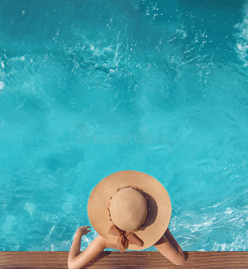 Back view of woman in straw hat relaxing in water swimming pool. At luxury villa resort. Summer holiday idyllic background. Vacations Concept. Exotic Paradise royalty free stock image