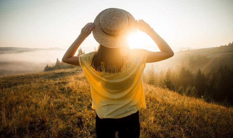 Back view of woman in straw hat stay outdoor under sunlight of sunrise with beautiful view of mountains stock photos